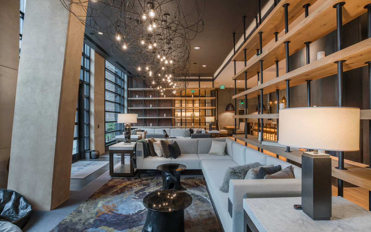 Sleek clubroom with L-shaped couch in The Belgard apartment