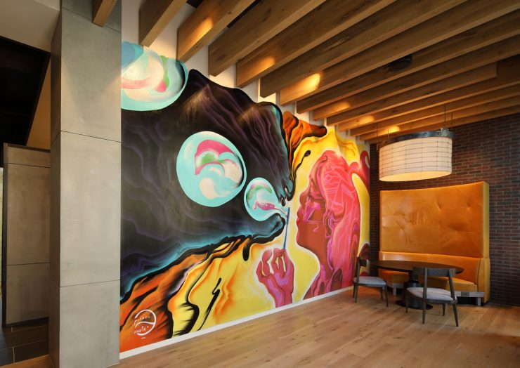 A custom designed mural near a seating area in The Belgard