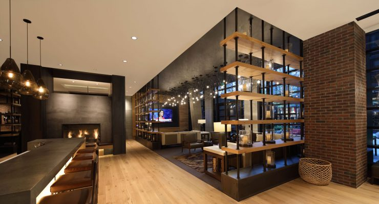 Sleek lounge with a fireplace with large screen TVs in The Belgard lobby