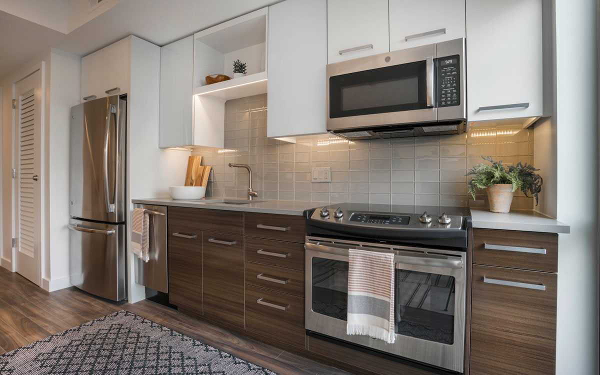 A new kitchen with chrome fixtures and appliances in a micro unit at The Belgard