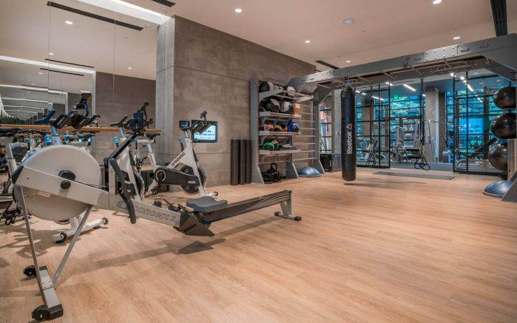 State-of-the-art fitness center featuring a rowing machine, a punching bag, and stationary bikes.