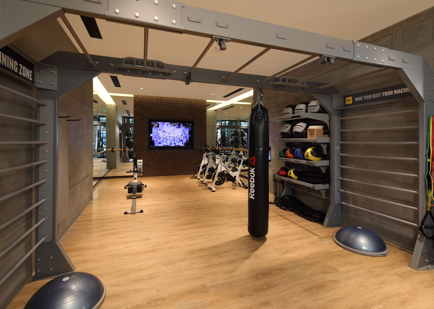 State-of-the-art fitness center featuring a punching bag, a rowing machine, free weight and stationary bikes.